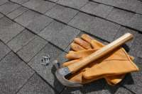 Shingles, Hammer and Nails on an Asphalt Shingle Roof