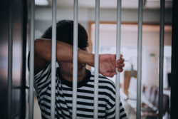 Inmate leaning on jail cell regarding visitations being cancelled at prisons and jails across Canada over the coronavirus