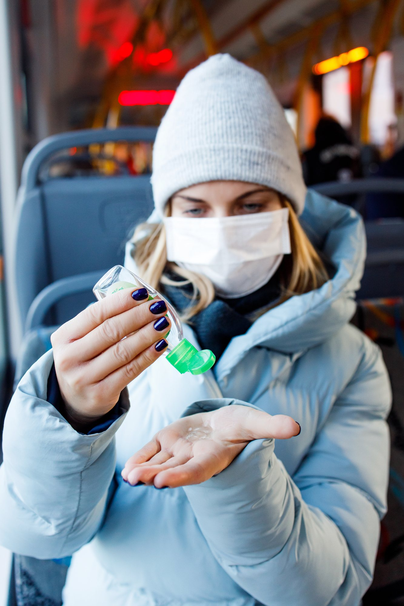 Woman wearing medical mask applying hand sanitizer regarding the Canadian consumer guide to the coronavirus